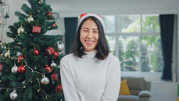アジアの女性はクリスマスフェスティバルを祝います。十代の女性は、クリスマスの帽子を着て幸せな笑顔を見てリラックスして自宅のリビングルームで一緒にクリスマス冬の休日をお楽しみください。