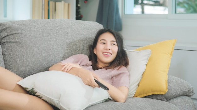 Молодая азиатская женщина подростка смотря тв дома, женщина чувствуя счастливый лежать на софе в живущей комнате. женщина образа жизни ослабляет в концепции утра дома.