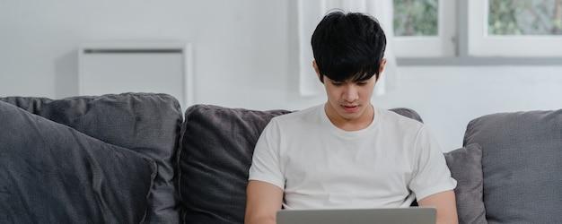 自宅で働いているフリーランスのアジア人男性、リビングルームのソファの上のラップトップで創造的な男性。ビジネスの若い男の所有者起業家、コンピューターをプレイ、現代の家で職場のソーシャルメディアをチェックします。