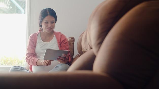 タブレット検索妊娠情報を使用して若いアジアの妊娠中の女性。自宅のリビングルームのソファーに横たわっている彼女の子供の世話をしながらママは前向きで平和な笑顔幸せを感じています。