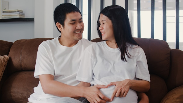 腹を保持している心のサインを作る若いアジア妊娠カップル。お母さんとお父さんは、赤ちゃんの世話をしながら平和な幸せな笑顔を感じて、妊娠は自宅のリビングルームのソファに横たわっています。