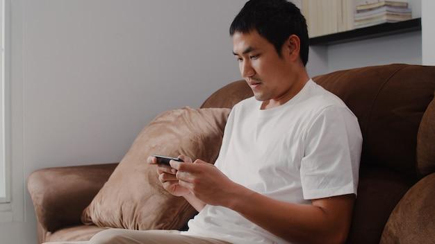 リビングルームでテレビでビデオゲームをプレイする携帯電話を使用して若い男性、自宅でソファに横たわってリラックスした時間を使用して幸せな感じの男性。男性は家でリラックスしてゲームをします。
