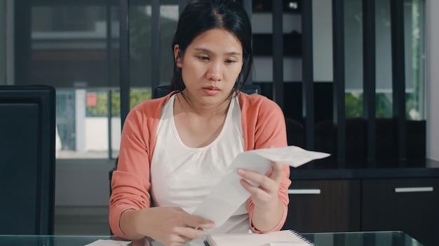 若いアジア妊婦の自宅での収入と支出の記録。ママは心配し、深刻で、ストレスを記録しながら、自宅の居間で働く予算、税金、財務書類を記録します。