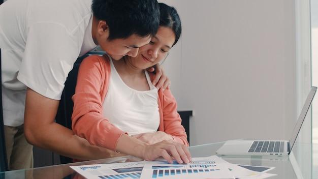 Молодая азиатская беременная женщина используя записи компьтер-книжки дохода и расходов дома. папа трогает живот своей жены, пока записывает бюджет, налоговые, финансовые документы, работая в гостиной дома