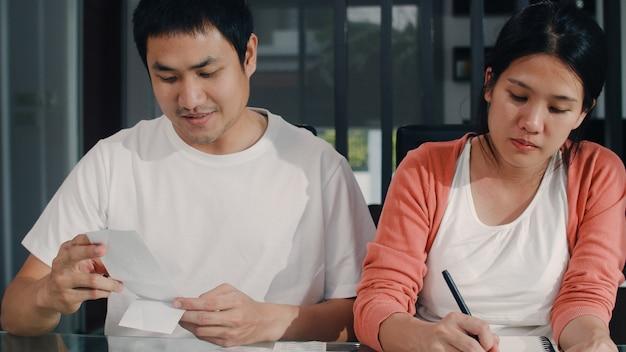 Молодые азиатские беременные пары регистрируют доходы и расходы дома. мама и папа счастливы, используя ноутбук рекордный бюджет, налог, финансовый документ, электронную коммерцию, работающую в гостиной дома.