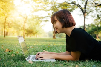 開いたラップトップと緑の草の上に若いアジアの女性の足
