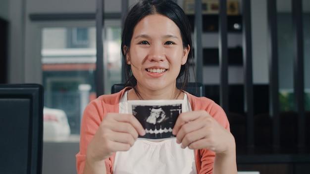 アジアの若い妊婦がお腹に超音波写真の赤ちゃんを見せて見ています。朝は自宅のリビングルームのテーブルの上に座って子供を世話しながら、平和な幸せな笑顔を感じているお母さん。