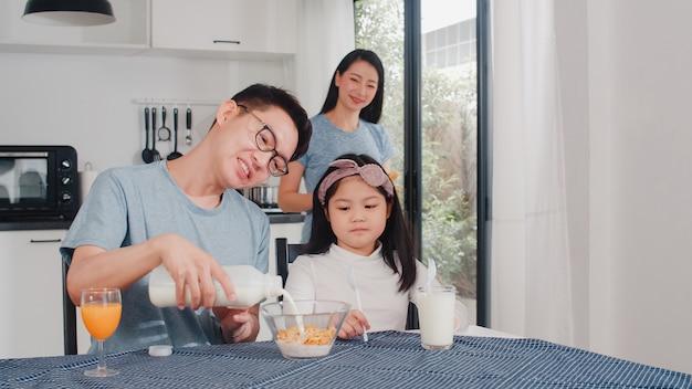 アジア系の日本人家族は家で朝食をとります。アジアのママ、パパ、娘は、朝、台所のテーブルの上のボウルでパン、コーンフレーク、シリアル、ミルクを食べながら一緒に話して幸せを感じています。