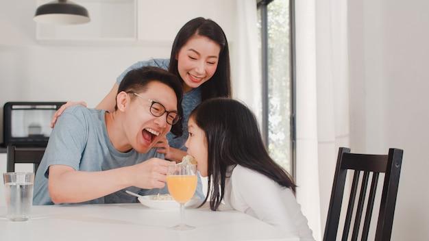 アジア系の日本人家族は家で朝食をとります。アジアの幸せなお父さん、お母さん、娘は、朝の家のモダンなキッチンのテーブルでスパゲッティドリンクオレンジジュースを食べます。