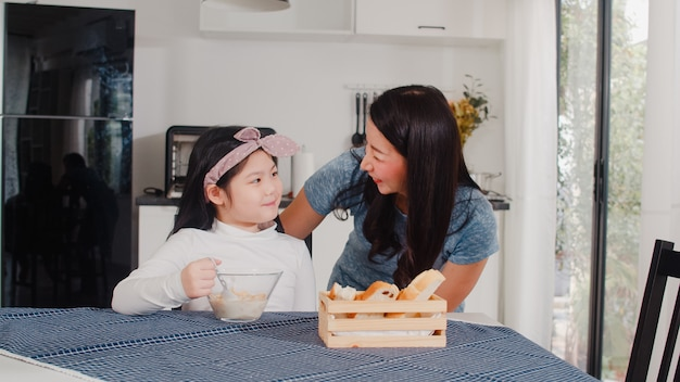 アジア系の日本人家族は家で朝食をとります。アジアのお母さんと娘は、朝の家でモダンなキッチンのテーブルの上のボウルにパン、コーンフレークシリアル、牛乳を食べながら一緒に話して幸せを感じます。