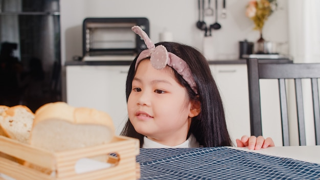 アジアの日本人の女の子は家でパンを食べる。朝は家のモダンなキッチンのテーブルの上のテーブルにそれを置く幸せなピックサンドイッチを感じているアジアの女性。