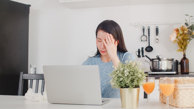 自宅での収入と支出の若いアジアビジネス女性記録。女性は、ラップトップの記録予算、税、家のモダンなキッチンで働く財務書類を使用しながら、深刻なストレスを心配しています。