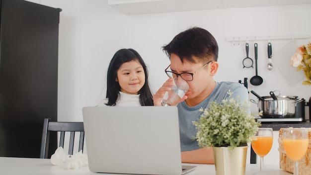 深刻な若いアジア系のビジネスマン、ストレス、疲れているし、自宅のラップトップに取り組んでいる間病気。朝、家のモダンなキッチンで一生懸命働く父親を慰める若い娘。