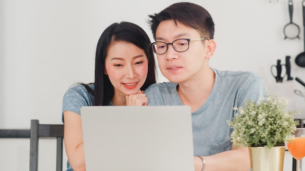 Молодые азиатские пары наслаждаются ходить по магазинам онлайн на компьтер-книжке дома. образ жизни молодой муж и жена счастливы купить электронной коммерции после того, как позавтракать в современной кухне дома утром.