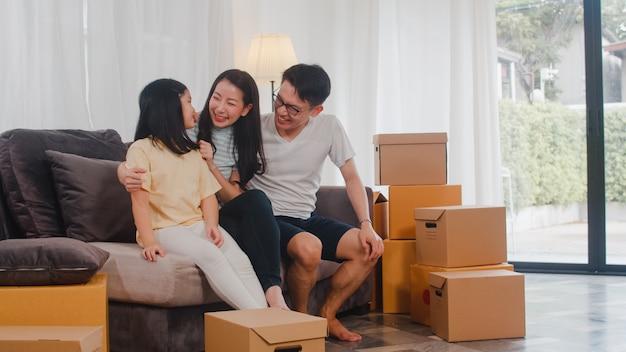 Счастливые азиатские молодые семейные домовладельцы купили новый дом. японские мама, папа и дочка обнимаются с нетерпением жду будущего в новом доме после переезда в переезд сидя на диване с коробками вместе.