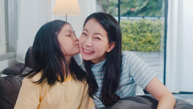 幸せな若いアジア家族ママと子供は自宅のソファで一緒に遊ぶ。子娘は幸せを楽しんでいる彼女のお母さんにキスし、夕方にはモダンなリビングルームで一緒に時間を過ごしてリラックスします。