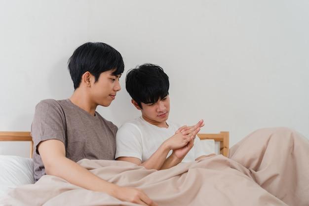 Красивые азиатские голубые пары говоря на кровати дома. молодой азиатский парень лгбтк + с удовольствием отдыхает вместе, проводит романтическое время после пробуждения в спальне в современном доме по утрам.