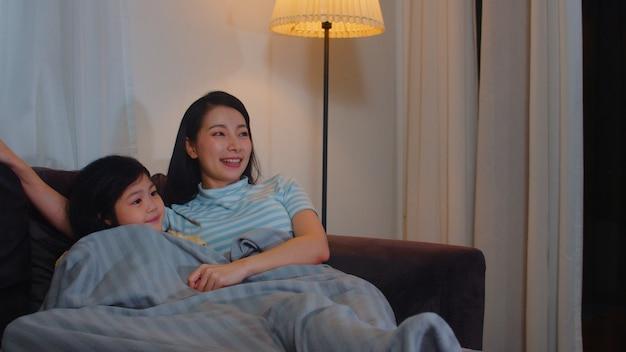 Молодая азиатская семья и дочь смотря тв дома в ноче. корейская мать с маленькой девочкой, счастливой, используя время семьи отдохнуть, лежа на диване в гостиной. веселая мама и милый ребенок веселятся.