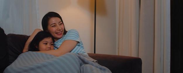 若いアジアの家族と娘が夜に家でテレビを見ています。家族の時間を使って幸せな少女と韓国人の母親は、リビングルームのソファに横たわってリラックスします。面白いママと素敵な子供が楽しんでいます。