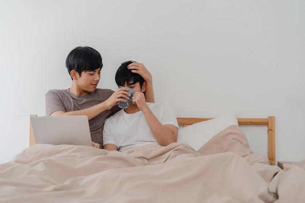 アジアのゲイの男性カップルは、コンピューターのラップトップを使用して、現代の家でコーヒーを飲みます。若いアジアの恋人男性幸せな目覚めた後、一緒に家で寝室のベッドに横になっている映画を見ながら一緒に残りをリラックスします。