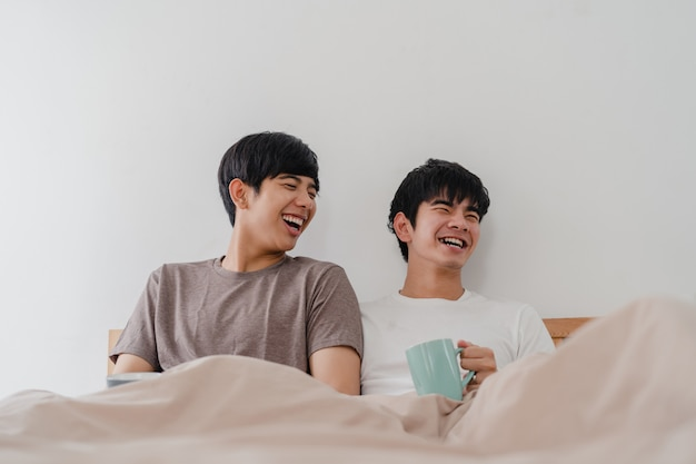 Азиатские гомосексуалисты соединяют говорить имеющ большое время на современном доме. молодой любитель азии мужчина счастливый расслабиться отдохнуть пить кофе после пробуждения лежа на кровати в спальне у себя дома в первой половине дня.
