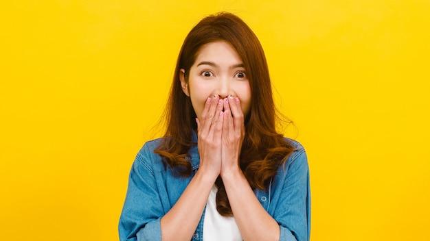 肯定的な表現、ファンキーなうれしそうな驚き、カジュアルな服を着て、黄色の壁越しにカメラを見ている若いアジア女性の肖像画。幸せな愛らしい喜んで女性は成功を喜ぶ。