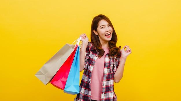 幸せな興奮してアジアの若い女性がカジュアルな服で立ち上がって黄色の壁を越えてカメラを見て手で買い物袋を運ぶします。顔の表情、季節限定セール、消費者のコンセプト。