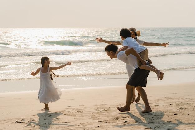 Азиатская молодая счастливая семья наслаждается каникулами на пляже в вечере. папа, мама и ребенок отдыхают, играя вместе возле моря, когда закат во время путешествия отпуск. образ жизни путешествия праздник каникулы лето концепция.