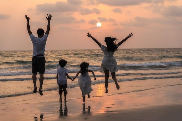 Азиатская молодая счастливая семья наслаждается каникулами на пляже в вечере. папа, мама и малыш отдыхать вместе работает возле моря во время силуэт заката. образ жизни путешествия праздник каникулы лето концепция.