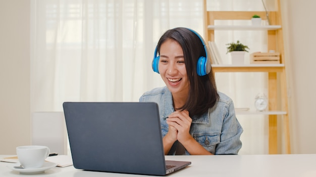 Носить внештатных бизнес-леди вскользь используя видео-конференцию звонка компьтер-книжки работая с клиентом в рабочем месте в живущей комнате дома. счастливая молодая азиатская девушка ослабляет сидеть на столе делает работу в интернете.