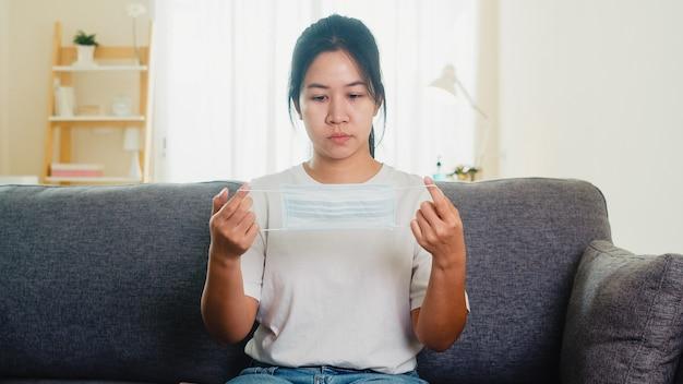 落ち込んでいるアジアビジネスの女性の社会的距離が家にいるとき、家のリビングルームのソファーに座っている防護マスクと自己検疫時間、中国でのパンデミック、コロナウイルスの概念。