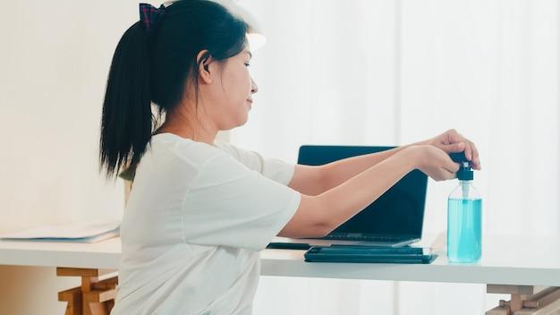 アルコールジェル消毒剤を使用してアジアの女性は、コロナウイルスを保護するために開いたタブレットの前に手を洗ってください。社会的距離が家にいるときと自己検疫時間にいるときの衛生のためにきれいにするアルコールを押す女性