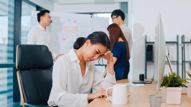 小さな近代的なオフィスの会議室でコンピューターデスクトップのプロジェクト研究問題で働いているミレニアル世代の若い中国人実業家。アジアの人々の職業バーンアウト症候群の概念。