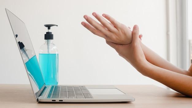 Азиатская женщина используя спирт гель дезинфицирующее средство мыть руки перед работой на ноутбуке для защиты коронавируса. женщина пьет алкоголь, чтобы убрать для гигиены, когда социальное дистанцирование остается дома и сам карантин времени.