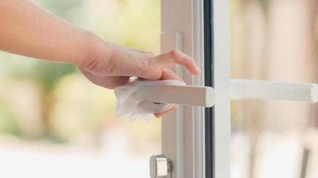 コロナウイルスを保護するためにドアを開ける前にティッシュクリーンドアノブにアルコールスプレーを使用しているアジアの女性。社会的距離が家にあるときの衛生のための女性のきれいな表面と自己検疫時間。