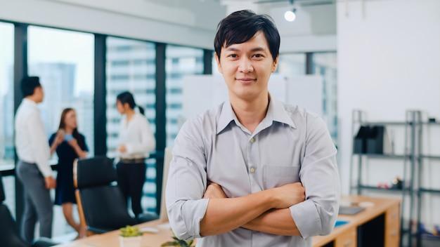 Портрет носки успешного красивого исполнительного бизнесмена умной вскользь смотря камеру и усмехаясь, оружия пересек в современное рабочее место офиса. молодой парень азии стоя в современном конференц-зале.