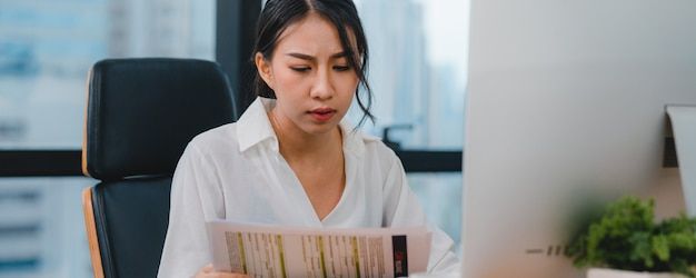 Тысячелетняя молодая китайская коммерсантка работая усилие вне с проблемой исследования проекта на настольном компьютере компьютера в конференц-зале на малом современном офисе. концепция синдрома профессионального выгорания людей азии.
