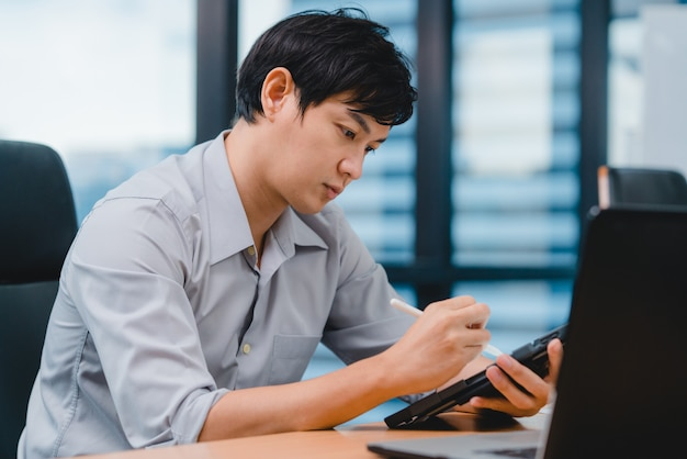 Чертеж вскользь носки успешного бизнесмена азии молодого руководителя умный, сочинительство и использование ручка с цифровым планшетом думая рабочего процесса идей поиска воодушевленности в современном офисе.