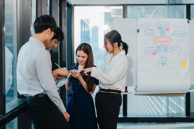創造的なオフィスで一緒に働いている間、コミュニケーションとテクノロジーを使用するスマートカジュアルウェアの多文化ビジネス人々の共同プロセスグループ。若い専門家のアジアチームが働いています。
