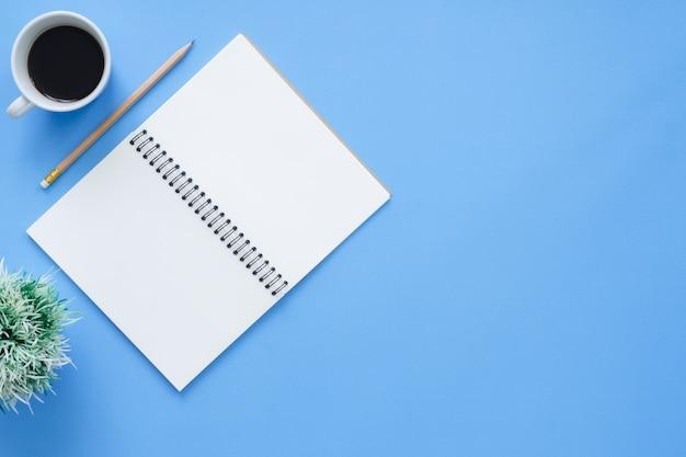 オフィス机の作業スペース - 白い空白のノートブックページを持つ作業スペースのフラットレイのトップビューモックアップ