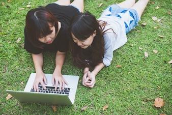 開いたラップトップと緑の草の若いアジアの女性の足