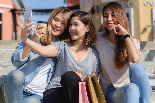 都市で買い物をしているときに魅力的な美しいアジアの女性スマートフォンを使用して