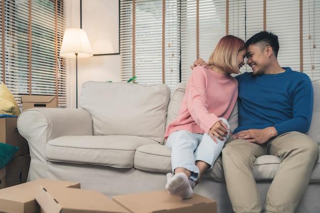 Сладкая счастливая молодая азиатская пара, перемещающая одежду и много предметов из старого дома в свой новый дом