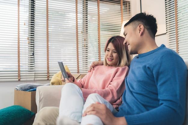 魅力的なアジアの甘いカップルは、リビングルームでリラックスしたときにソファに横になってタブレットを使用