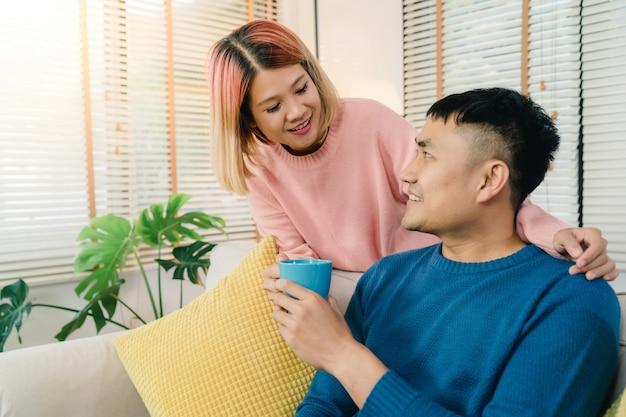 魅力的なアジアの甘いカップルは、彼らの手でコーヒーやお茶の暖かいカップを飲むのが好き