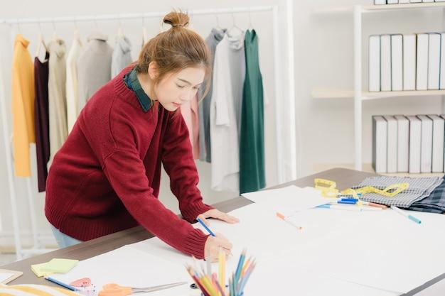 ファブリックスケッチを扱うプロフェッショナルな美しいアジアの女性ファッションデザイナー