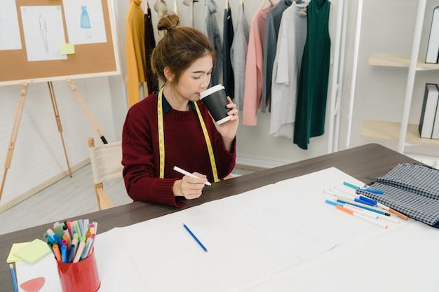 Профессиональный красивый азиатский модельер, работающий с эскизами ткани