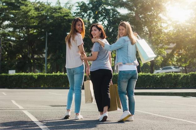 Группа молодых азиатских женщин, покупки на открытом рынке с сумок в руках