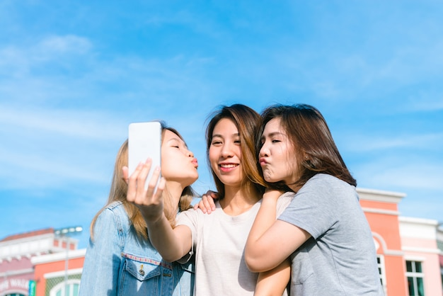 若いアジア人女性のグループは、買い物の後、パステルの町の電話でセルフをする