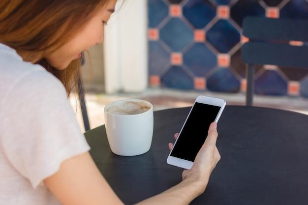 スマートフォンを使用している若いアジア人の女性は、カフェで空白の黒い画面をモックアップ